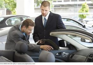 Car salesman serving a male client